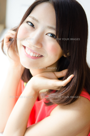 髪を触りながら笑っている女性の素材 [FYI01077761]