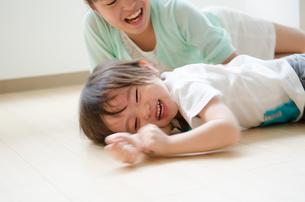 床に転がって笑っている男の子の素材 [FYI01077767]