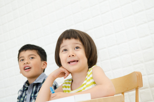 イスに座って何かを見ている子供たちの素材 [FYI01077774]