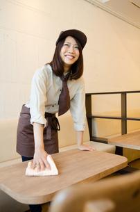 制服を着てテーブルを拭く女性の素材 [FYI01077783]