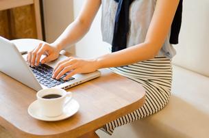 カフェでノートパソコンで仕事をしている女性の手元の素材 [FYI01077786]