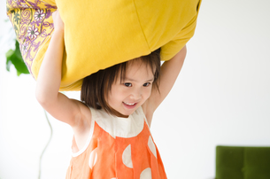 クッションを頭の上に乗せている女の子の素材 [FYI01077787]