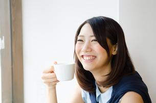 コーヒーカップを持って笑う女性の素材 [FYI01077795]