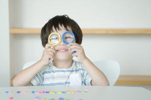 虫眼鏡を使って遊んでいる子供の素材 [FYI01077805]