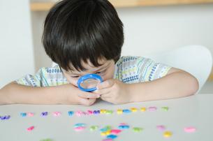 アルファベットを虫眼鏡で見ている子供の素材 [FYI01077848]