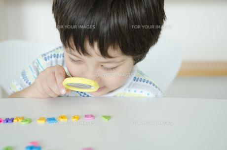 アルファベットを虫眼鏡で見ている子供の素材 [FYI01077863]
