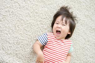 ラグに寝転んで笑っている男の子の素材 [FYI01077871]