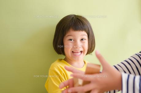 ブロックが崩れるのを見て笑う女の子の素材 [FYI01077881]