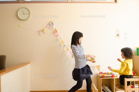 家の飾りつけをしている女の子たちの素材 [FYI01077884]