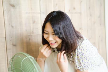 扇風機に向かって笑っている女性の素材 [FYI01077885]