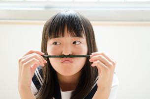 鉛筆を鼻の下に挟んでいる制服姿の女の子の素材 [FYI01077886]
