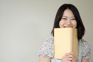 本を持って笑っている女性の素材 [FYI01077892]