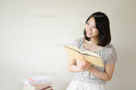 本を持って笑っている女性の素材 [FYI01077896]