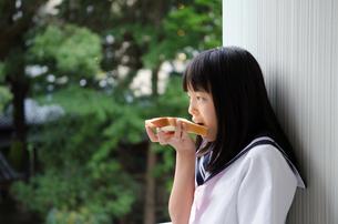 壁にもたれかかってパンを食べている制服姿の女の子の素材 [FYI01077899]