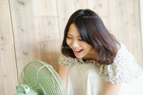 扇風機に向かって声を出している女性の素材 [FYI01077906]