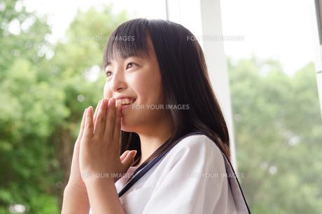 手を合わせて笑う女子高生の素材 [FYI01077910]