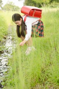 ランドセルを背負って小川の側にいる女の子の素材 [FYI01077911]