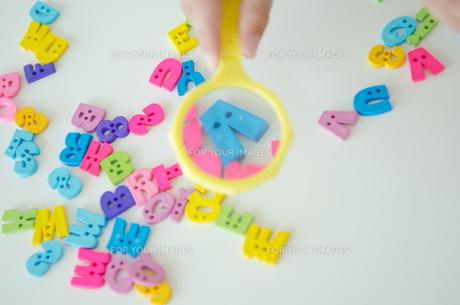 虫眼鏡でアルファベットを見ている子供の手の素材 [FYI01077912]