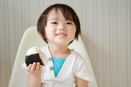 おにぎりを持って笑っている男の子の素材 [FYI01077924]