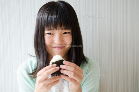 おにぎりを持って微笑んでいる女の子の素材 [FYI01077928]