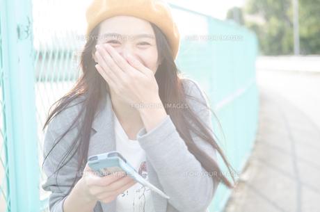 スマホを持って笑っている女性の素材 [FYI01077930]