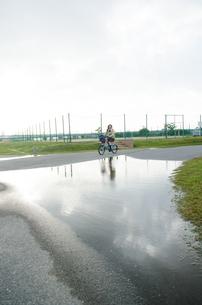 大きな水溜りの横を通る自転車の素材 [FYI01077937]
