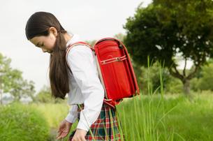 ランドセルを背負って草むらにいる女の子の素材 [FYI01077941]