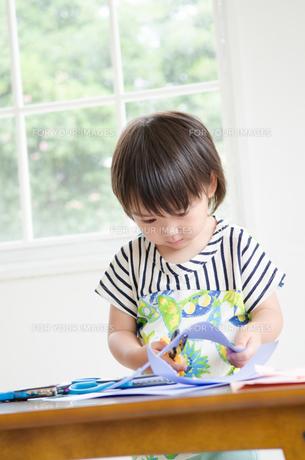 紙を切っている男の子の素材 [FYI01077948]