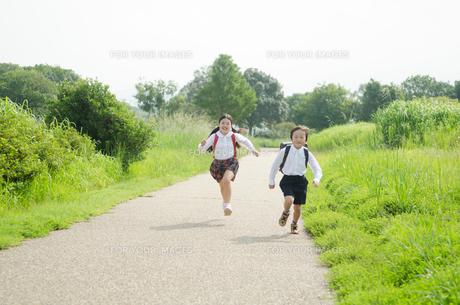 ランドセルを背負って走る小学生2人の素材 [FYI01077949]