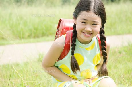 ランドセルを背負って草むらに座っている女の子の素材 [FYI01077952]