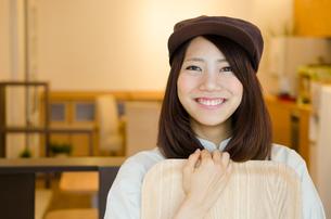 制服を着てカフェで働く女性の素材 [FYI01077959]