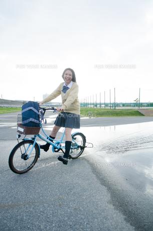 水溜りを通る自転車に乗った学生の素材 [FYI01077961]