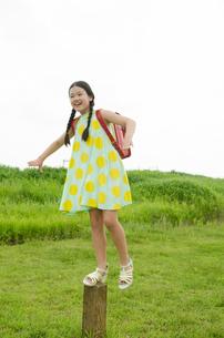 ランドセルを背負ってくいの上に立っている女の子の素材 [FYI01077980]