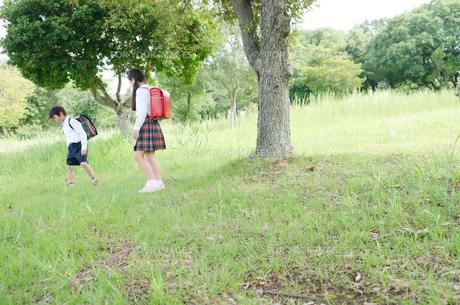 ランドセルを背負って草むらを歩く子供たちの素材 [FYI01077981]