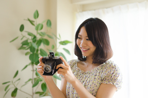 クラシックカメラを見ている笑顔の女性の素材 [FYI01077987]