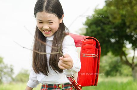 ランドセルを背負って棒を持っている女の子の素材 [FYI01077996]