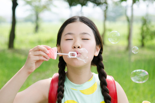 ランドセルを背負ってシャボン玉を吹いている女の子の素材 [FYI01078009]