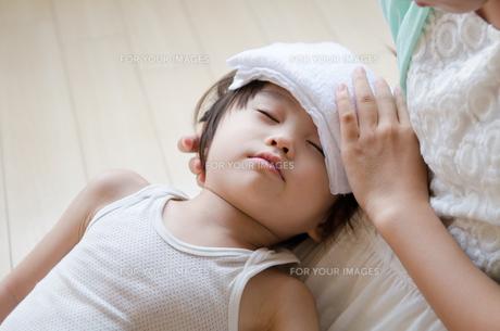 タオルを額の上に乗せて目をつぶっている男の子の素材 [FYI01078012]