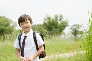 ランドセルを背負って草むらにいる男の子の素材 [FYI01078026]