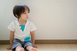 床に座って横を見ている男の子の素材 [FYI01078037]
