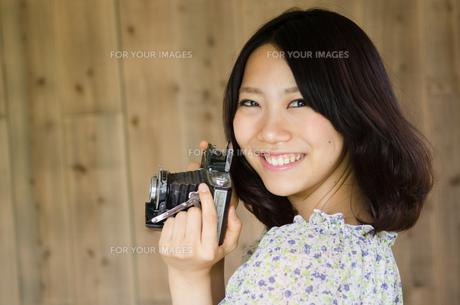 クラシックカメラを構えて笑っている女性の素材 [FYI01078046]