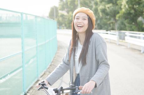 自転車のハンドルを持って笑っている女性の素材 [FYI01078070]