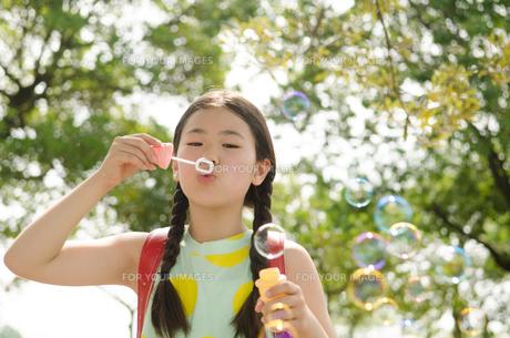 ランドセルを背負ってシャボン玉を吹く女の子の素材 [FYI01078071]