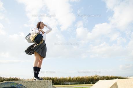 立って遠くを見ている女子学生の素材 [FYI01078072]
