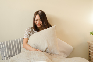 ベッドで枕を抱える女性の素材 [FYI01078084]