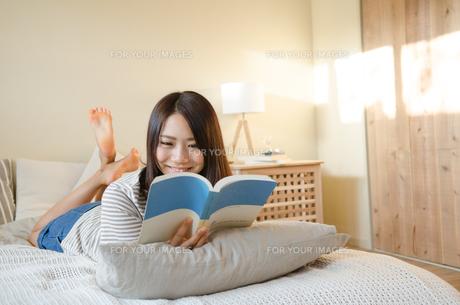 ベッドで本を読んでいる女性の素材 [FYI01078091]