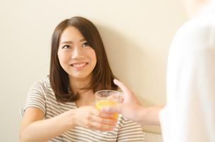 オレンジジュースを受け取る女性の素材 [FYI01078102]