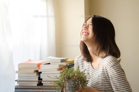 観葉植物を持って笑っている女性の素材 [FYI01078106]