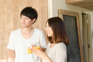 オレンジジュースを持っているカップルの素材 [FYI01078107]