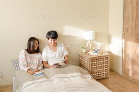 ベッドの上で本を読むカップルの素材 [FYI01078110]